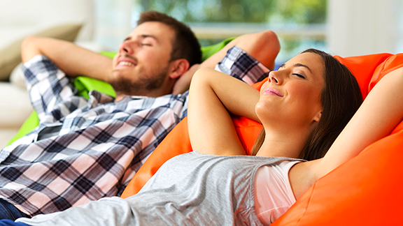 Couple on Couch taking a deep breath in